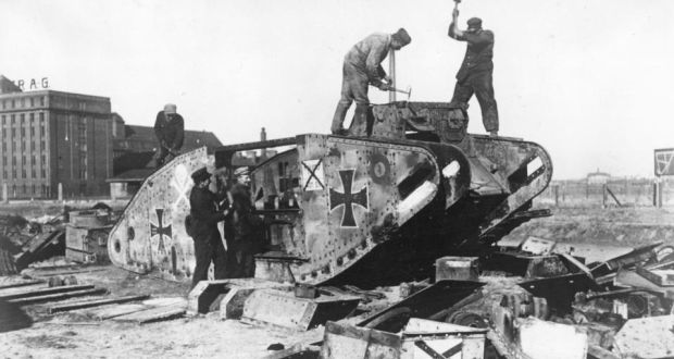 1919: Germans take war machines apart outside Berlin. Under the terms of the Treaty of Versailles Germany was required to disarm. This tank is in fact a British tank, captured and put into service by the Germans. Photograph:  Hulton Archive/Getty Images